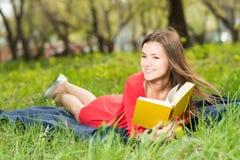 美丽的女孩在公园读书 免版税图库摄影