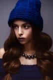 美丽的女孩在冬天编织了与项链的帽子蓝色颜色在珍珠的脖子上 与精美构成和s的年轻模型 库存图片