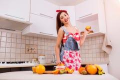 美丽的女孩在准备晚餐的厨房里 免版税库存图片