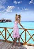 年轻美丽的女孩在别墅sundeck的桃红色sundress在水的,马尔代夫站立 库存图片