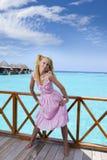 年轻美丽的女孩在别墅sundeck的桃红色sundress在水的,马尔代夫站立 免版税图库摄影