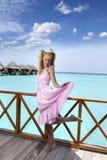 年轻美丽的女孩在别墅sundeck的桃红色sundress在水的,马尔代夫站立 免版税库存照片