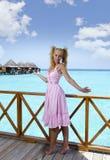 年轻美丽的女孩在别墅sundeck的桃红色sundress在水的,马尔代夫站立 图库摄影