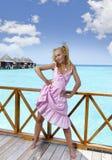 年轻美丽的女孩在别墅sundeck的桃红色sundress在水的,马尔代夫站立 免版税库存图片