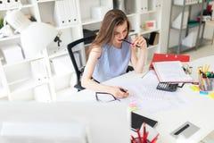美丽的女孩在办公室在她的手上坐在桌上,拿着一个黄色标志并且咬铅笔 库存图片