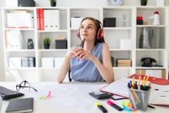 美丽的女孩在办公室在手上坐在红色耳机的一张桌上并且拿着一支铅笔 免版税库存照片