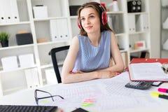 美丽的女孩在办公室坐在红色耳机的一张桌上 库存图片