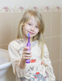 美丽的女孩在卫生间显示一把电牙刷 免版税图库摄影