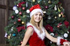 美丽的女孩在圣诞老人衣服穿戴了在圣诞树附近 库存照片
