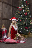 美丽的女孩在圣诞老人衣服穿戴了在圣诞树附近 免版税库存照片