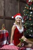 美丽的女孩在圣诞老人衣服穿戴了在圣诞树附近 库存图片