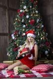 美丽的女孩在圣诞老人衣服穿戴了在圣诞树附近 图库摄影