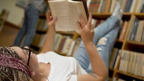 美丽的女孩在地板读说谎一本的书在图书馆里 股票视频