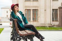 美丽的女孩在外套和帽子休息穿戴了,坐与闭合的眼睛的一条长凳 库存图片