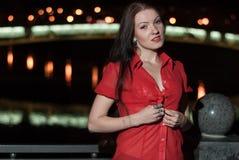 美丽的女孩在夜河诱人地脱下衣服 免版税库存图片