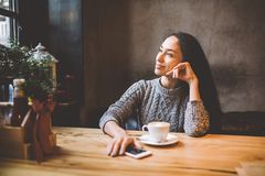 美丽的女孩在她的在用圣诞节装饰装饰的咖啡馆的手机旁边喝从一个白色杯子的咖啡, 免版税库存图片