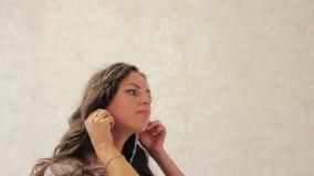 美丽的女孩在她的婚礼之日戴着耳环 股票视频