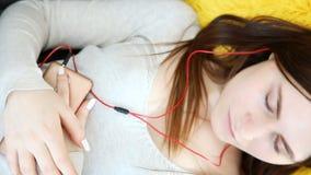 美丽的女孩在家听到与手机的音乐在沙发的耳机 股票录像