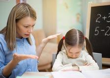 美丽的女孩在家教与横征暴敛的母亲 俏丽的学员年轻人 免版税图库摄影