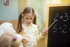 美丽的女孩在家教玩具在黑板 学龄前家庭教育 免版税库存图片
