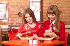 美丽的女孩在寿司店吃寿司卷。 免版税图库摄影