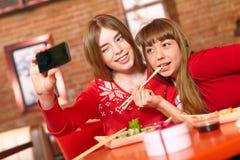 美丽的女孩在寿司店吃寿司卷。 库存照片