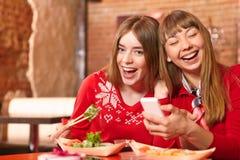 美丽的女孩在寿司店吃寿司卷。 图库摄影