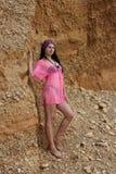 美丽的女孩在岩石附近的海边 免版税库存照片