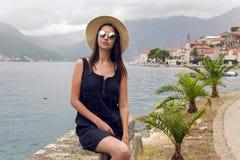 美丽的女孩在帽子坐山和海背景  免版税库存图片