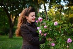 美丽的女孩在庭院在手上拿着桃红色玫瑰 库存图片