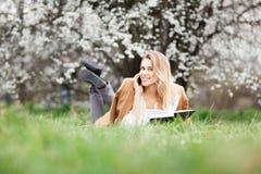 美丽的女孩在开花庭院里在一个春日 库存图片