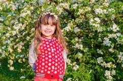 美丽的女孩在开花的庭院里 免版税库存照片