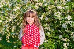美丽的女孩在开花的庭院里 免版税库存图片