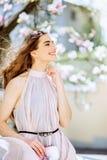 美丽的女孩在开花的树中站立 开花白色 有她的头发的春天女孩在一件米黄礼服 免版税库存图片