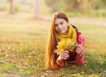 美丽的女孩在户外五颜六色的秋天 库存图片