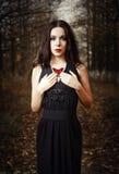 美丽的女孩在手上拿着红色蝴蝶。室外画象 库存图片