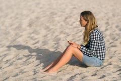 美丽的女孩在手上的拿着一个智能手机在海滩在海岸沙子附近在背景中 库存照片