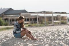 美丽的女孩在手上的拿着一个智能手机在海滩在海岸沙子附近在背景中 免版税库存照片