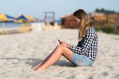 美丽的女孩在手上的拿着一个智能手机在海滩在海岸沙子附近在背景中 免版税库存图片