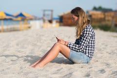 美丽的女孩在手上的拿着一个智能手机在海滩在海岸沙子附近在背景中 库存图片