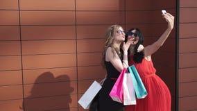 美丽的女孩在手机照相机做记忆的portert 朋友在购物以后做selfie 白肤金发和深色  影视素材