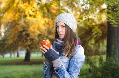 美丽的女孩在拿着柿子果子的公园 免版税库存照片