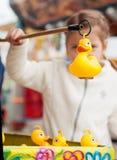 美丽的女孩在捉住玩具鸭子的游乐园 Du 免版税库存图片