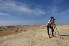 年轻美丽的女孩在接近Farafra绿洲的惊人的白色沙漠中间拍照片在埃及 库存照片