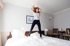 美丽的女孩在旅馆里跳滑稽在双人床上 免版税库存照片