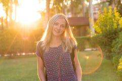 年轻美丽的女孩在日落的公园在晴天 库存照片