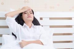 美丽的女孩在早晨,说谎在一件白色衬衣的一张白色床上有头疼/失眠/偏头痛/重音的 免版税库存照片