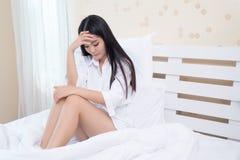 美丽的女孩在早晨,说谎在一件白色衬衣的一张白色床上有头疼/失眠/偏头痛/重音的 库存图片