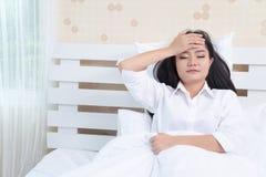 美丽的女孩在早晨,说谎在一件白色衬衣的一张白色床上有头疼/失眠/偏头痛/重音的 免版税库存图片