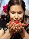 美丽的女孩在春天的嗅到新鲜的草莓 免版税库存照片